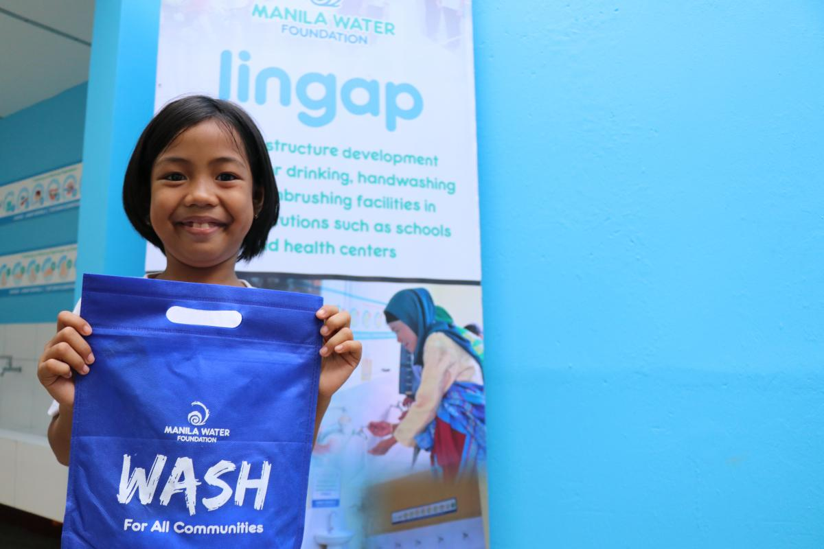 A student from Tudturan Elementary school shows off a hygiene kit from Manila Water Foundation.