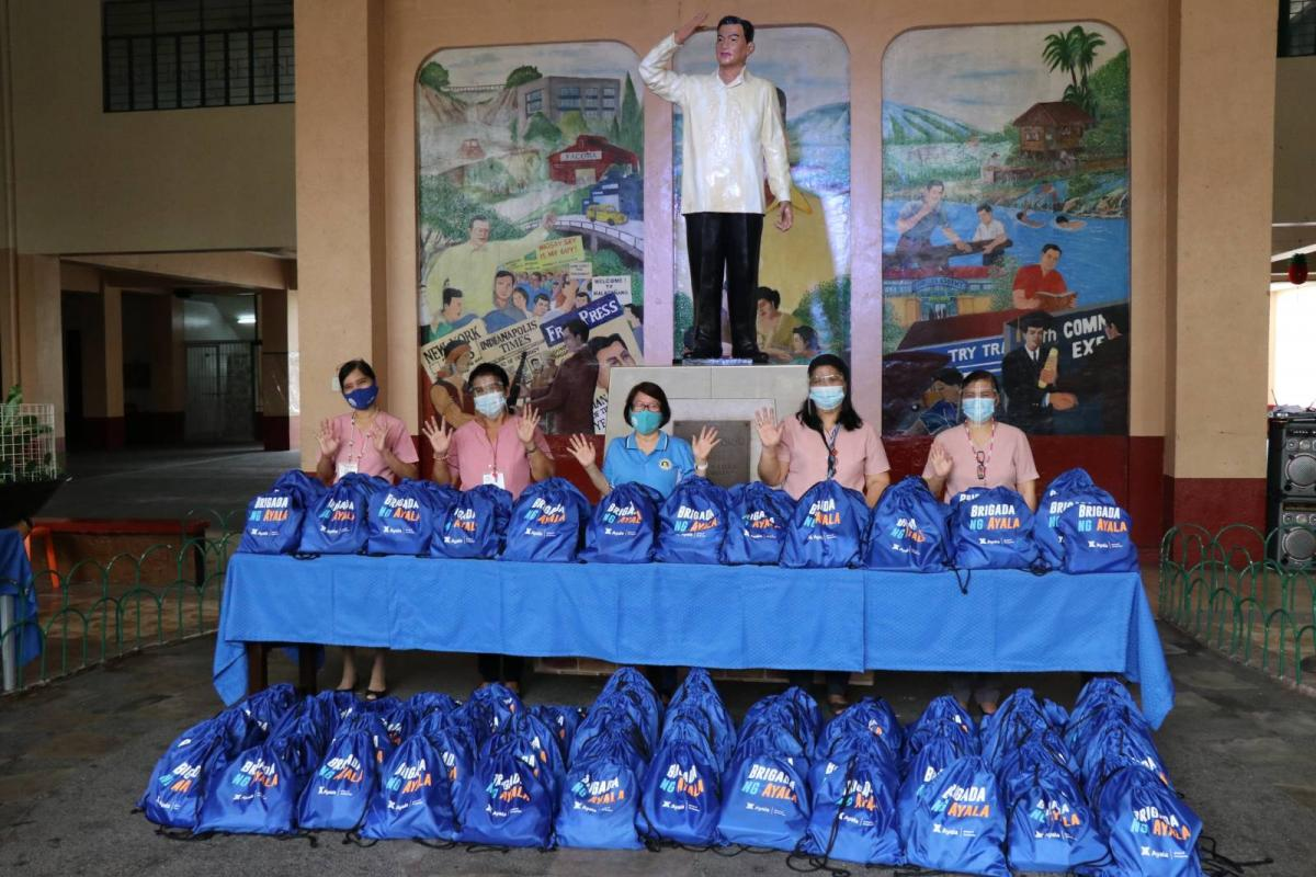 Ramon Magsaysay High School teachers and staff happily receive 200 Brigada ng Ayala Educare packs for their students and staff